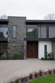 Designed by David James Architects in Dorset, England. The blend of stone, render, glass and aluminium making up the street facade creates visual contrasts with the iroko timber gate.: