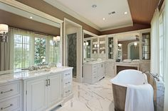 white tones, from tile flooring to painted wood cabinetry, this bathroom features large mirrors all around and a window side pedestal tub