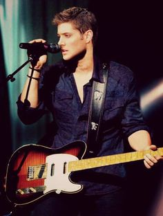 Jensen playing acoustic electric guitar and singing