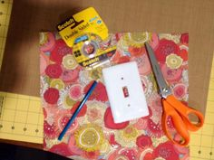 Supplies: light switch plate, fabric or paper, scissors, double-sided tape (optional).....