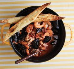 The classic Tuscan seafood soup Cacciucco is made with a base of squid, tomatoes, wine, garlic, sage, and chiles, then other fish are added right before serving.