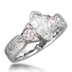 Wow - just wow. Mokume Three Stone Engagement Ring, Tapered, Marquise and Trilliants -from Krikawa.com   This designer mokume three stone engagement ring  features a marquise center stone embellished by fancy pink diamond side  stones. A band of mokume gane tapers towards the setting.