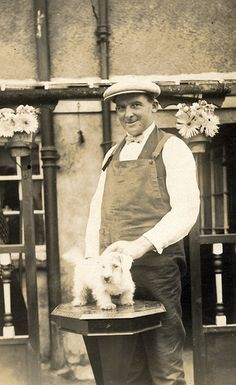 Vintage photo of man in overalls and a hat with a small white terrier puppy.