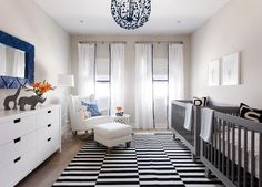 Blue and gray twin boys' nursery features a blue lantern, Stray Dog Designs Celeste Sphere, illuminating a pair of matching gray cribs, Oeuf Sparrow Cribs, placed side by side under baby animal prints by The Animal Print Shop atop a black and white striped rug, Ikea Stockholm Rug.
