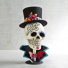Cheese! Posing for the camera, our Day of the Dead sugar skull bust is smiling ear to ear in vibrant color. Celebrate life in gorgeous contrast to our gentleman skeleton that's dressed for the occasion in a floral studded top hat. If you like to mix a little grim with glitter, this Pier 1 exclusive is a perfect choice.