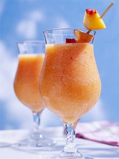 Peach Daiquiris  (3  cups pitted, peeled, and sliced fresh peaches, frozen (thawed) unsweetened peach slices  1/2  of a 12-oz can frozen limeade or lemonade concentrate, thawed  1/4  cup light rum   2  Tbs powdered sugar  2  to 3 cups ice cubes    Fresh peach chunks)
