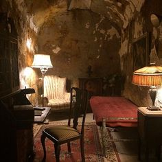 """Al Capone's sumptuous cell in Eastern State Penitentiary. This years brilliantly put on """"Terror Behind the Walls"""" haunted prison event this year ended with a cocktail party in the old, abandoned prison's """"Park Avenue"""" of cells. Al Capone was interred here between 1929-1930, following his arrest for carrying a concealed fire arm outside a movie theatre in Philadelphia on Market Street. According to the Philadelphia Public Ledger, Capone's cell was """"cheery and homelike.....included a cabinet…"""