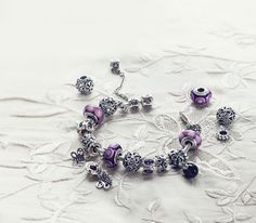 Pandora has these add-your-own-charms bracelets...$25-$60 for each charm...
