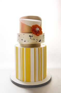 AMBER | Charm City Cakes Summer 2013 Collection Yellow stripes dorm the large base of this three tiered cake. Middle layer is white with black splashed spots,  and finished with a rose and white timeless topper.