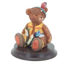 Decorative collectible resin teddy bear figurine.  A boy teddy bear is sitting on a round wooden round base, the boy bear is dressed as an Indian and is holding a bow and quiver with arrows. #EverythingsCollectible #CollectItAll #Bear #Figurine