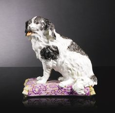 A Meissen figure of a spaniel circa 1745 -  seated to the left with its long-haired coat marked in dark grey, its open mouth revealing a flesh-coloured tongue, raised on a rectangular puce cushions painted with purple and gilt flowers and foliage, crossed swords mark in underglaze-blue, 24cm., 9½in. high