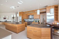 Contemporary kitchen with slate countertops and teak wood cabinets.