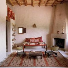 I like this combination of plastered walls, rustic beams and Moroccan textiles!
