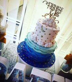 moon and stars in gold, decorating a two-layered cake, with frills in three shades of blue, little white clouds, and a gold cake topper