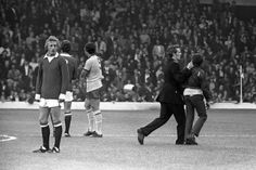 Soccer - League Division One - Manchester United v Arsenal - Anfield, Liverpool Manchester United's Denis Law waits patiently as a Policeman grabs a youth by his ear and leads him off the pitch. Manchester United were banned from playing at home for the first two games of the season following hooliganism at Old Trafford the previous season. Archive-PA153218-2a Ref #: PA.12586519  Date: 20/08/1971....17