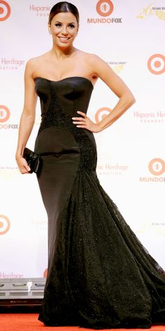 EVA LONGORIA At the 26th Hispanic Heritage Awards, Eva Longoria went all out in a black embellished strapless Versace gown with a red carpet-sweeping train. She kept everything else to a minimum, choosing to wear diamond studs and to carry a small unimposing black clutch.