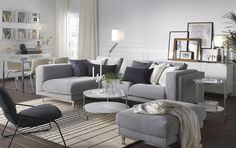 A light living room furnished with a light grey two-seat sofa combined with a chaise longue. Shown together with a round coffee table on castors and a light grey footstool.
