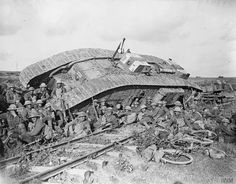 Battle of Cambrai. Men of the 20th Battalion, Manchester Regiment (25th Division) resting by a tank (serial number 9891), disabled by side-slipping down a railway embankment. Near Premont, 8 October...