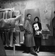 1955, London, England, UK --- A man and woman stand in a phonograph listening booth at a music store in London. 1955.