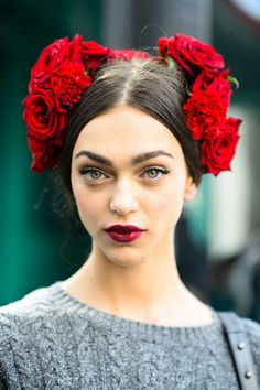 Her red lips and green eyes match the roses perfectly! We can't look away. #MFW #beauty