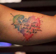 Tattoo particolari piccoli e femminili, idea con una scritta piccola e cuore intorno colorato a schizzi