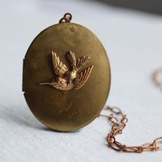 This great locket features an incredibly detailed, three-dimensional hummingbird set on a large oval locket. I really like the contrast between the tiny hummingbird and the oversized locket.  Both the locket and hummingbird charm are vintage and are solid brass and copper. I have added a coppery brass chain which measures 28. Because this locket is large, it is designed to be worn fairly long, well below the chest.  The locket is vintage, so has a bit of tarnishing and maybe a couple of…
