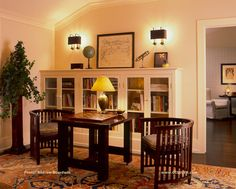 A large space in a hallway in a shingle-style house on Long Island was made useful and cozy with glass fronted doors on bookcases, vintage 1920's steel sconces from France, American Arts & Crafts table and Indonesian barrel chairs, antique table lamp and an antique Persian area rug. www.GISSLER.com