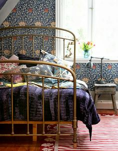 Deep blue walls, wall above bed in blue & yellow William Morris paper, light grey linen bedclothes, with shots of deep gold / mustard in cushions, eiderdown, paintings.