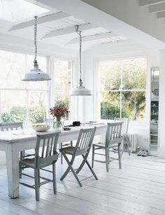 white + fresh room:  walls of windows; simple farmhouse table w/slatted chairs; industrial pendants; beamed ceiling