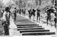 Burma-Thailand Railway. c. 1943. Prisoners of war (POWs) carrying sleepers in Burma, about forty kilometres south of Thanbyuzayat. (Probably Beke Taung) (Donor A. Seary)