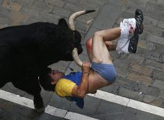 "Diego Miralles gets gored by a bull on Estafeta street during the sixth running of the bulls of the San Fermin festival in Pamplona July The runner, a man from Castellon, Spain, was gored three times. ""Gored"" Photo by Susana Vera."