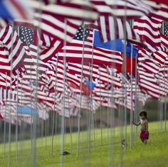A boy stands amongst 3000 US flags are displayed at Pepperdine University to mark the 14th anniversary of the 9/11 terror attack September 10 2015 in Malibu California. by parismatch_magazine