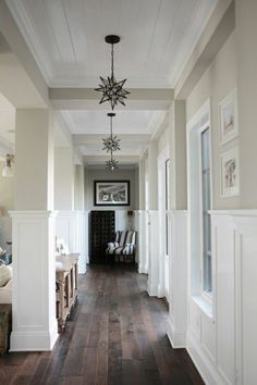 black and white star-shaped lamps, hanging from a white ceiling, inside a corridor with pale beige walls, with white paneling, hallway decor ideas, dark solid wooden floor