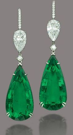 Emerald and diamond earrings.  Two hypnotic green pear-shaped emeralds, weighing 23.55 and 23.66 carats are found floating beneath two pear-shaped diamonds, weighing 2.01 and 2.14 carats. The hooks are pave-set with small diamonds and are mounted on platinum.