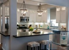 kitchen with painted white cabinets, stainless steel appliances and dark countertops. How to update oak cabinets ideas