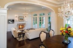 I want to hang a chandelier above the fireplace like that.  So cute!