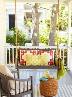 Unify mismatched furniture with a fresh coat of paint and accent with boldly patterned pillows. More porch ideas: http://www.midwestliving.com/homes/outdoor-living/45-ideas-for-warm-and-welcoming-porches/?page=5