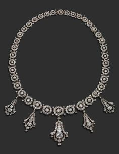 A late Victorian diamond necklace. Formed with graduated circular links, each centred with a cushion-shaped diamond within a surround of smaller cushion-shaped diamonds in cut-down gold and silver collets and each joined with two smaller diamonds. Suspending five detachable and graduated diamond-set pendants. #Victorian #necklace