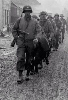 Bastogne Belgium Soldiers of the 28th Infantry Division US Army,march down a street in Bastogne December 20th 1944 during The Battle of the Bulge