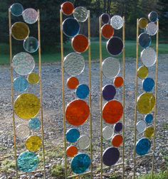"Stained glass garden art stake in yellow, light teal blue and clear irridescent textured glass with solid brass frame. The glass section is 24"" and the legs are 10"" long, giving you lots of length to stick in the ground. Overall dimensions are 4"" wide and 34"" tall.    The garden art stakes begin by me constructing the frame, selecting the colors, hand cutting the glass and soldering the circles securely to the brass frame. The brass frame ensures against any rust and my design allows the…"