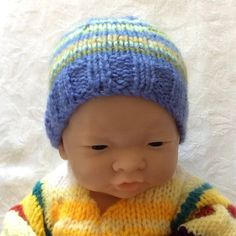 A dear little hat for a new baby or a dolly! Modelled in photos by a baby doll. Hat knitted in wool. Stripes of blue, aqua and lime - with a touch of cream and purple