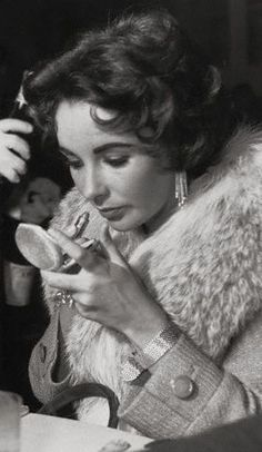 Elizabeth Taylor touching up her makeup.
