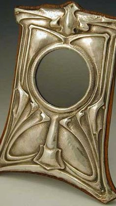 This mirror is from the Art Nouveau movement. The obvious curvature of the lines in the relatively simple embellishments is an indicator of this. Also the silver colouring being a prominent part of the mirror.