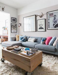 Sala de estar tem mesa de centro de pinus e sofá azul claro com almofadas estampadas.