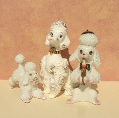 Here is a lot of three, fun, vintage retro style poodles. The largest spaghetti poodle is 5 high and 3 1/2 long with a sassy look on her face. Shes in great shape without any chips, cracks or crazing and is marked D-589 X on the bottom. The poodle holding the candle has a textured surface and is 4 1/4 high. He has a small chip on the back of his beret, but otherwise is in good shape and is marked Japan on the bottom. The third crouching poodle is also textured with two pink flowers....