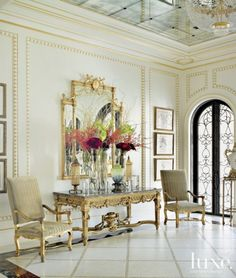 Honey onyx mosaic tiles from Trinity Tile intersect the flooring in the foyer, where shimmering gold leaf accents the millwork. More gold appears in the form of the gilt Louis XVI console, from the owners' collection, and the Adam-style mirror and 19th-century Régence-inspired armchairs from William R. Eubanks. The botanical art is from Jerry Pai.