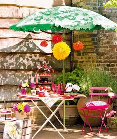 Shady Lady    Warm weather calls for bright colors and lively details. Accessorize a folding table with a hot pink bistro chair, green umbrella, and fluffy multicolored paper pom-poms.