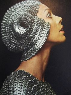 """Paco Rabanne, 1974 Metalwork headpiece and dress  Rabanne, known as the """"l'enfant terrible"""" of 1960s fashion design, got his start in the fashion industry by designing jewelry for luxury labels like Balenciaga, Dior and Givenchy. In 1966, he launched is own eponymous label marked by distinctive, avant-garde designs using odd materials like metal, paper and plastic."""