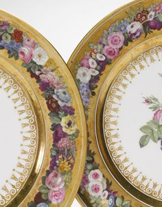 TWO SÈVRES PLATES CIRCA 1809 each finely painted in the center with a colorful flower arrangement within a gold-ground border decorated with a garland of summer flowers, both with red printed and partially erased factory marks, one dated 1809, the other with date partially erased.