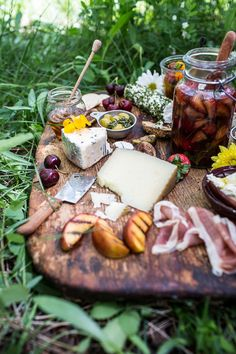 Modern Rustic Decor: Part of your engagement party decor is how your food and wine are displayed. This tasty charcuterie platter features seasonal ingredients arranged on a gorgeous wooden cutting board. Condiments and veggies are placed in various mismatched containers like tin measuring cups and glass jars. Even though they are all different, together they create a modern-rustic vibe.